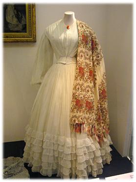 19世紀半ばのコットンドレスと大流行したカシミールショール。ショールのオレンジ色に合わせた襟元のコーラルが洒落ています。